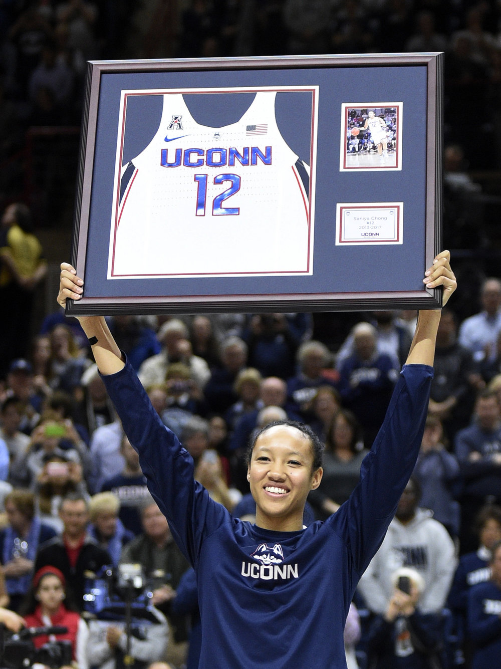 Connecticut's Saniya Chong holds aloft a plague on senior day before the team's NCAA college basketball game against Memphis in Storrs, Conn., Saturday, Feb. 25, 2017. Connecticut won the game 91-48. (AP Photo/Fred Beckham)