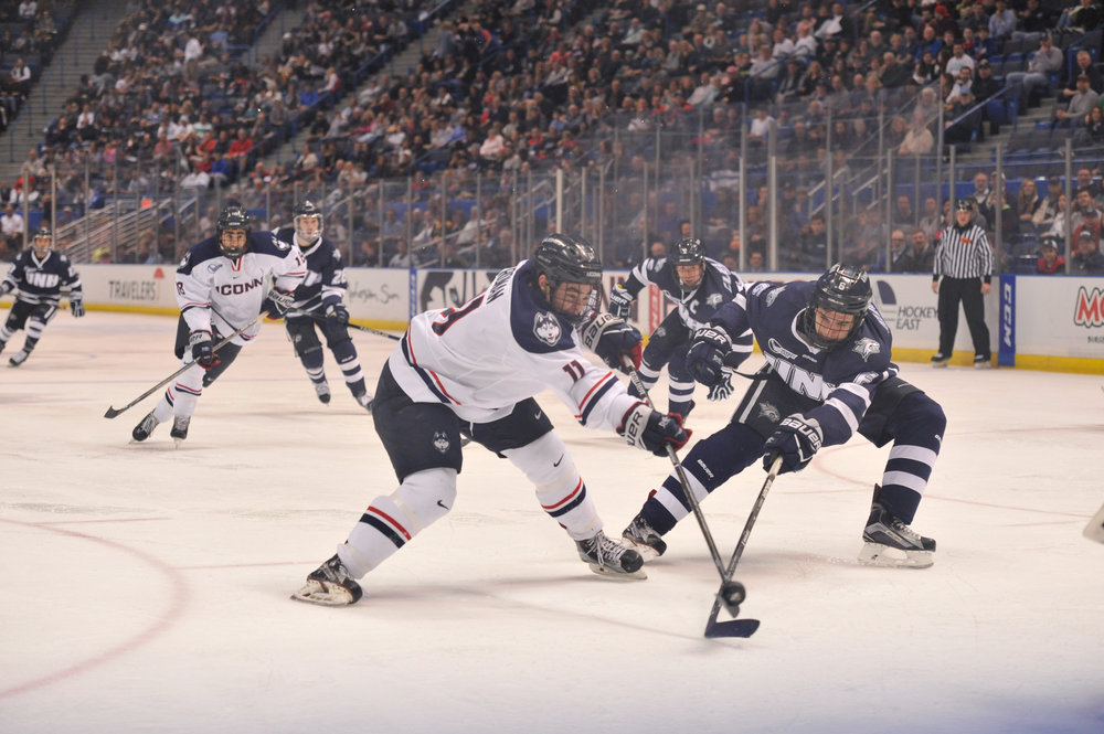 Corey Ronan (11) fights a UNH defender for the puck during the Huskies 4-2 victory over UNH on Feb. 22, 2017 at the XL Center in Hartford. (Jason Jiang/The Daily Campus)