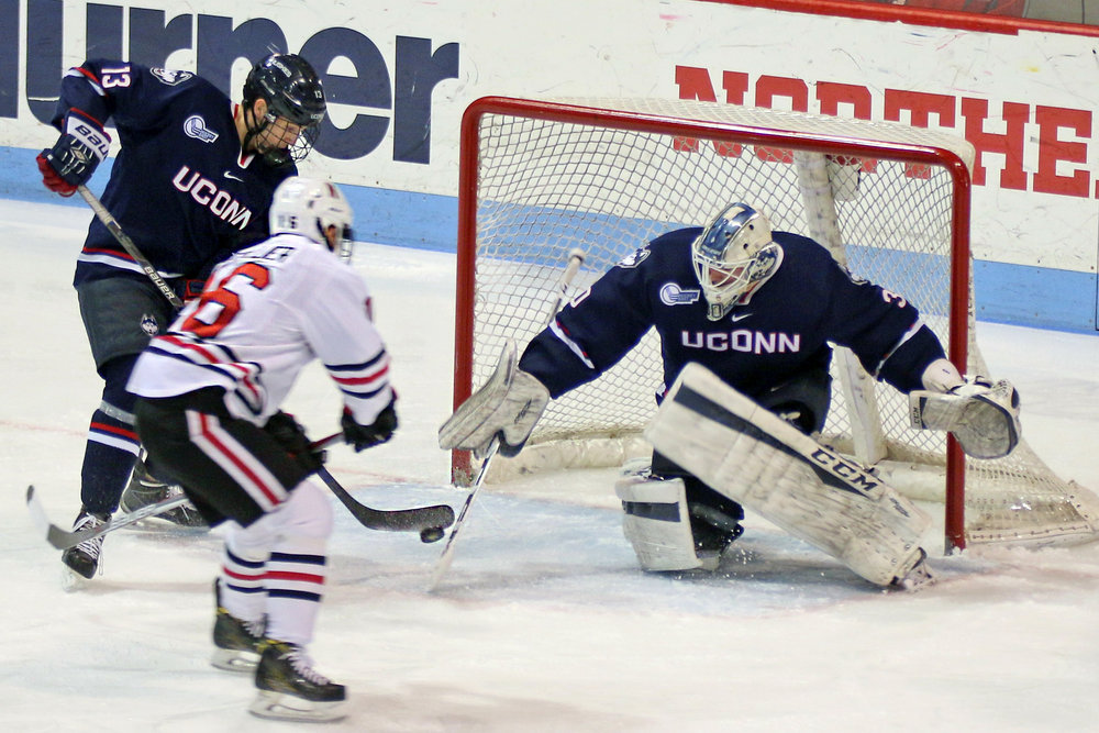 Northeastern's Brendan Collier shoots at UConn goaltender Adam Huska in NU's 6-2 win over UConn at Matthews Arena in Boston, Massachusetts on March 4, 2017 in the Hockey East Tournament quarterfinals. (Ian Bethune/The UConn Blog)