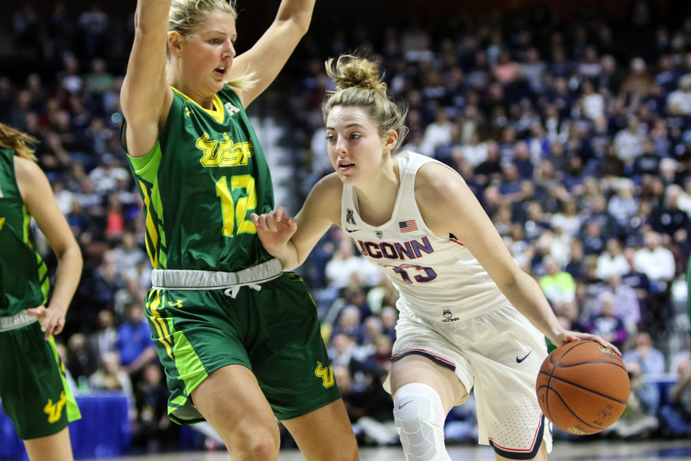 UConn sophomore Katie Lou Samuelson drives to the hoop against USF's Maria Jespersen during Monday night's AAC title game at Mohegan Sun Arena. Samuelson scored 40 points, including perfect 10-for-10 shooting from 3 point range, to lead the Huskies to a 100-44 victory over the Bulls. (Jackson Haigis/The Daily Campus)