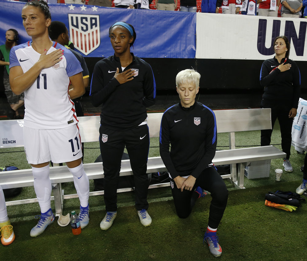 In this Sunday, Sept. 18, 2016, file photo, USA's Megan Rapinoe, right, kneels next to teammates Ali Krieger (11) and Crystal Dunn (16) as the U.S. national anthem is played before an exhibition soccer match against Netherlands, in Atlanta. (John Bazemore/AP)