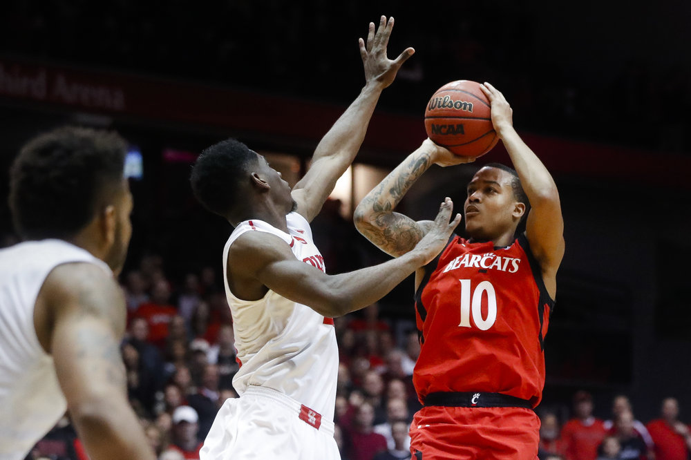 Cincinnati's Troy Caupain (10) shoots over Houston's Damyean Dotson, center, during the second half of an NCAA college basketball game, Thursday, March 2, 2017, in Cincinnati. Cincinnati won 65-47. (John Minchillo/AP)