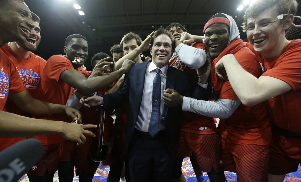SMU head coach Tim Jankovich, center, celebrates winning the American Athletic conference with his players after an NCAA college basketball against Memphis Saturday, March 4, 2017, in Dallas. SMU won 103-62. (LM Otero/AP)