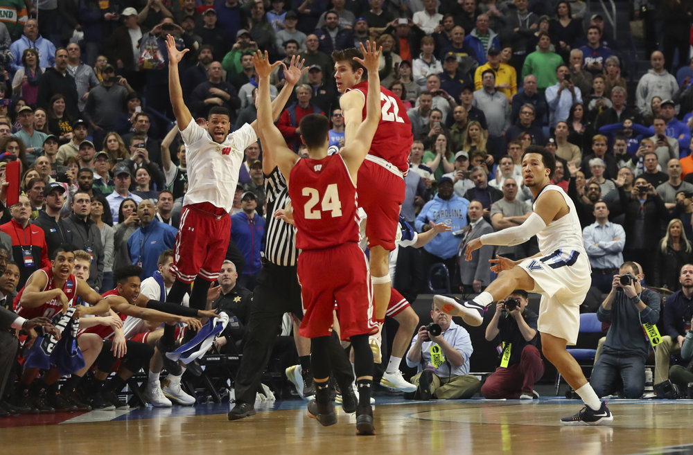 Villanova guard Jalen Brunson (1) follows through on a final shot as Wisconsin players celebrate the end of their second-round men's college basketball game in the NCAA Tournament, Saturday, March 18, 2017, in Buffalo, N.Y. (AP Photo/Bill Wippert)