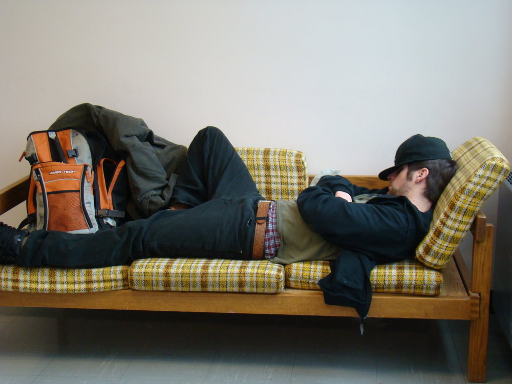 A student catching up on sleep in between classes is not an unusual sight on college campuses. The transition from Spring Break back to campus is not an easy one, as the author points out in his weekly 'Lazy Boy' column. (Judy/Creative Commons)