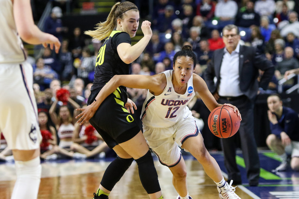 UConn senior Saniya Chong blows by Oregon's Sabrina Ionescu as head coach Geno Auriemma looks on. Chong scored 11 points, 9 of which came from three-pointers.