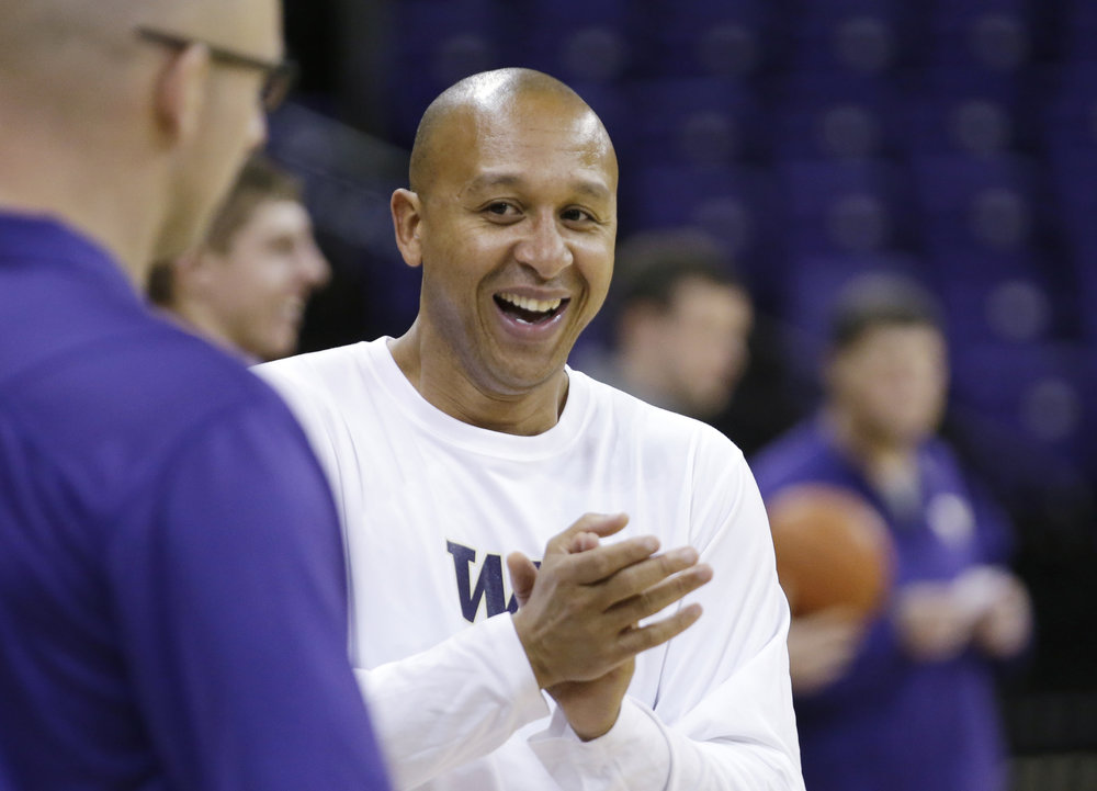 Washington assistant coach Raphael Chillious applauds the team effort at basketball practice Tuesday, Oct. 8, 2013, in Seattle. (Elaine Thompson/AP)