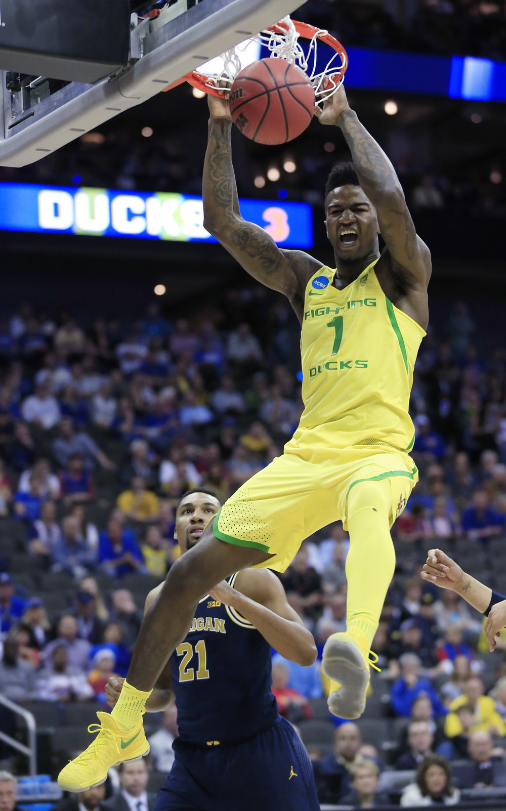 In this Thursday, March 23, 2017, file photo, Oregon forward Jordan Bell (1) dunks over Michigan guard Zak Irvin (21) during the first half of a regional semifinal of the NCAA men's college basketball tournament in Kansas City, MO. (Orlin Wagner, File/AP)
