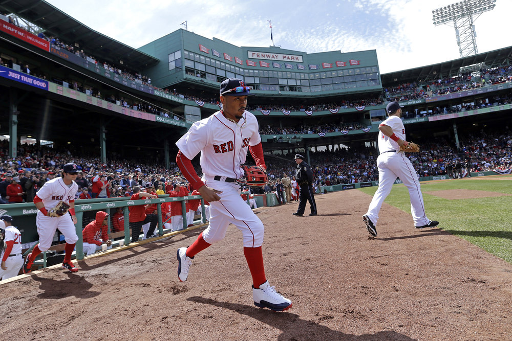Boston Red Sox players including Mookie Betts, middle, take the field for the start of their baseball home opener against the Pittsburgh Pirates at Fenway Park, Monday, April 3, 2017, in Boston. (Elise Amendola/AP)