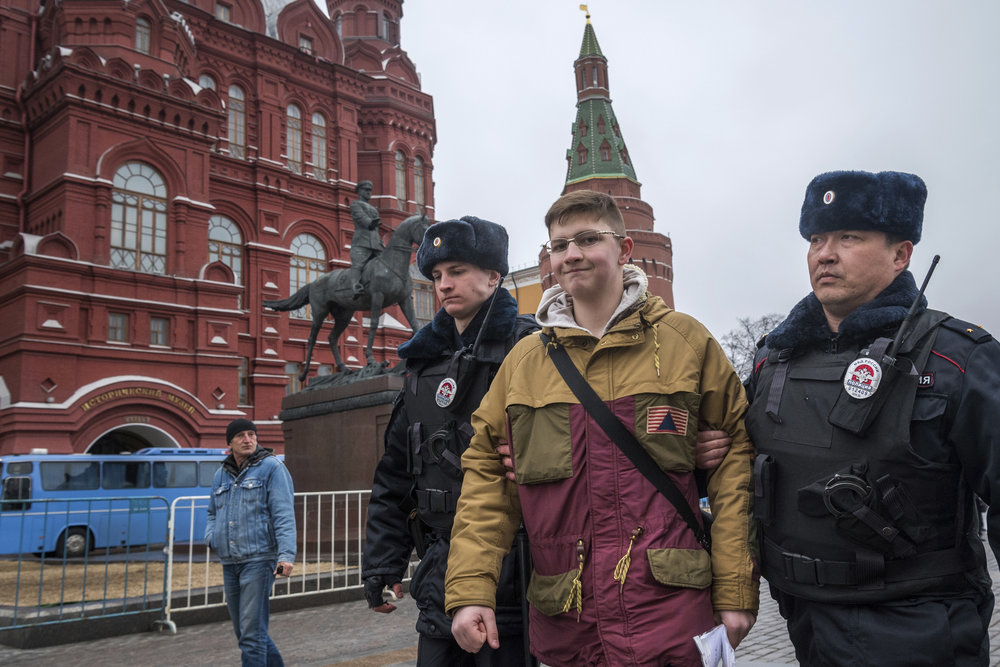 Police officers detain a school boy in front of the Historical Museum near Red Square in anticipation of a possible opposition action in Moscow, Russia, Sunday, April 2, 2017. (AP Photo/Ilya Varlamov)