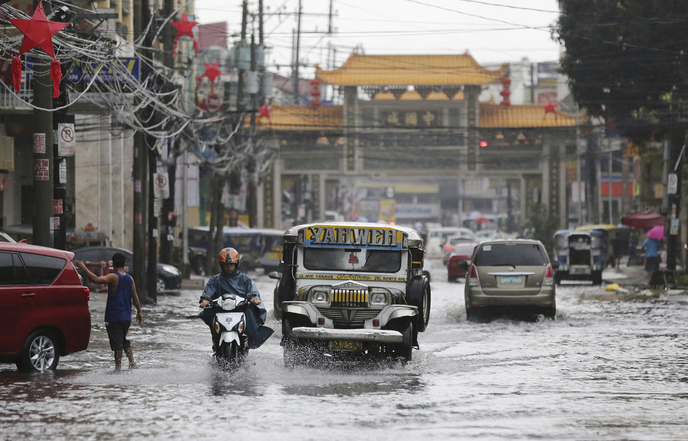 A passenger jeep navigates a flooded street caused by rains from Typhoon Nock-Ten in Quezon city, north of Manila, Philippines on Monday, Dec. 26, 2016. The powerful typhoon slammed into the eastern Philippines on Christmas Day, spoiling the biggest holiday in Asia's largest Catholic nation, where a governor offered roast pig to entice villagers to abandon family celebrations for emergency shelters. (Aaron Favila/AP)