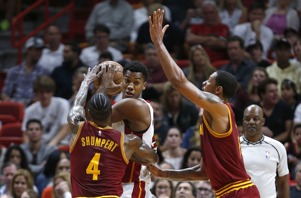 Miami Heat center Hassan Whiteside, center, looks for an opening past Cleveland Cavaliers guard Iman Shumpert (4) and forward Channing Frye during the first half of an NBA basketball game, Monday, April 10, 2017, in Miami. (AP Photo/Wilfredo Lee)