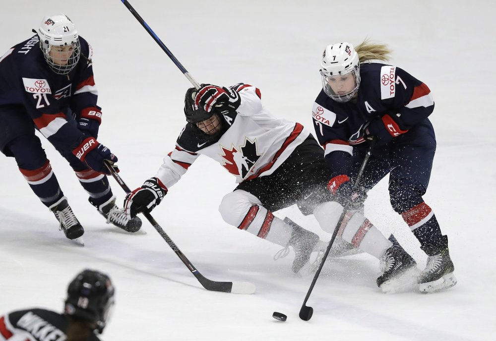 U.S. forward Hilary Knight (21) and defender Monique Lamoureux (7) reach for the puck next to Canada forward Brianne Jenner (19) during the first period of the gold-medal game of the women's world hockey championships, Friday, April 7, 2017, in Plymouth, Mich. (Carlos Osorio/AP)
