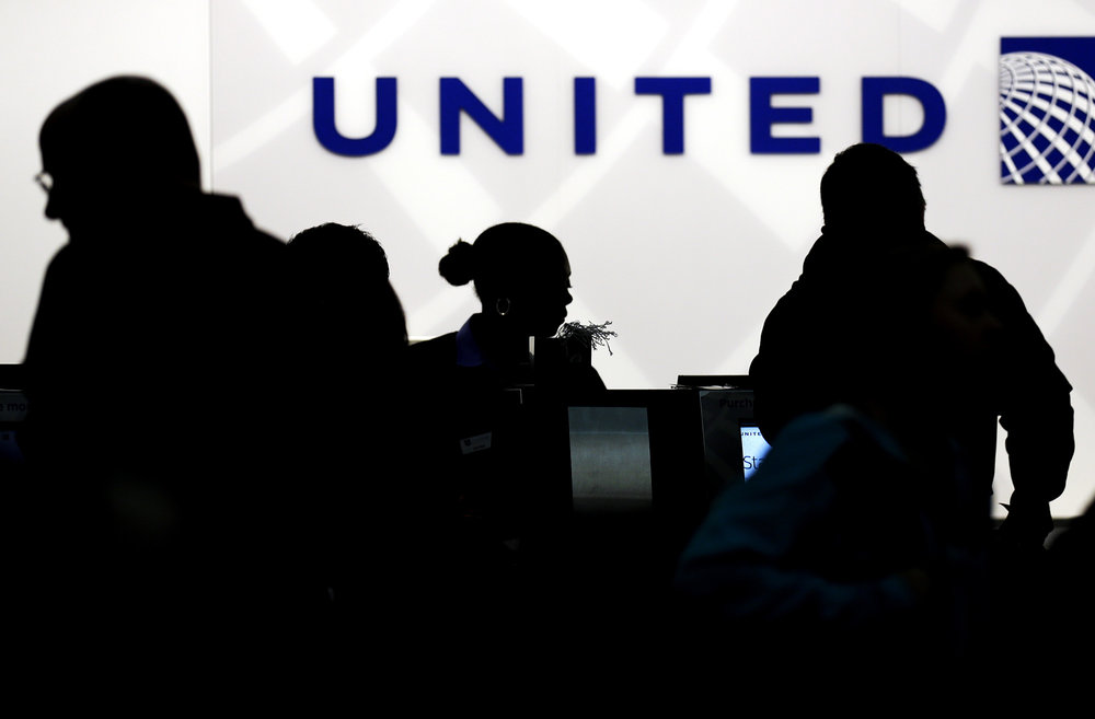 In this Saturday, Dec. 21, 2013, file photo, travelers check in at the United Airlines. After a man is dragged off a United Express flight on Sunday, April 9, 2017, United Airlines becomes the butt of jokes online and on late-night TV. Travel and public-relations experts say United has fumbled the situation from the start. (Nam Y. Huh/AP)