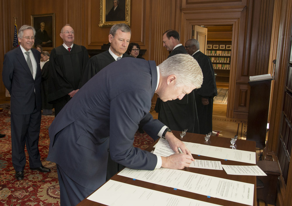 In this photo provided by the Public Information Office Supreme Court of the U.S., Chief Justice John Roberts, Jr., and fellow justices watch as Neil Gorsuch signs the Constitutional Oath after Roberts administered the Constitutional Oath in a private ceremony, Monday, April 10, 2017, in the Justices' Conference Room at the Supreme Court in Washington.  (Franz Jantzen/ AP)