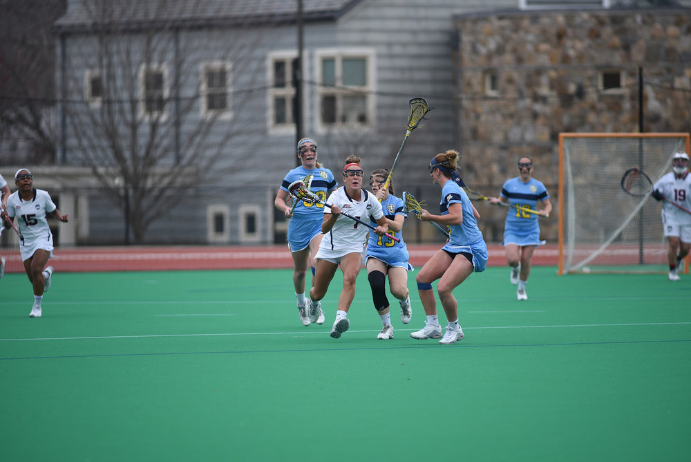 The Huskies defeated Marquette 17-14 on Wednesday, April 12. Pictured is freshman, Olivia Miles (number 1) vs Marquette opponenets. (Charlotte Lao/ The Daily Campus)