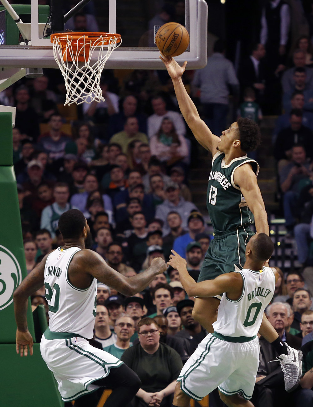 Milwaukee Bucks guard Malcolm Brogdon (13) puts up a shot ahead of Boston Celtics forward Amir Johnson (90) and Avery Bradley (0) during the first half of an NBA basketball game, Wednesday, March 29, 2017, in Boston. (Mary Schwalm/AP)