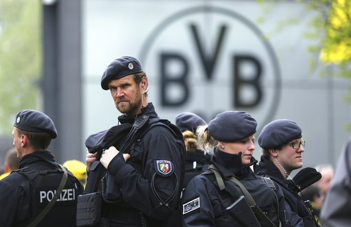 Police guard at the entrance of the Dortmund stadium prior to the German Bundesliga soccer match between Borussia Dortmund and Eintracht Frankfurt, in Dortmund, Saturday, April 15, 2017. Defender Marc Bartra and a police officer were wounded when three explosions hit the team bus as it was leaving for the stadium ahead of the first leg of the Champions League quarterfinal against Monaco Tuesday, April 11, 2017. (Ian Fassbender/dpa via AP)