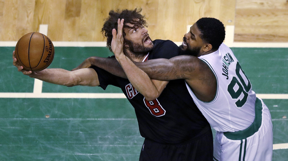 Boston Celtics forward Amir Johnson (90) fouls Chicago Bulls center Robin Lopez (8) during the first quarter of a first-round NBA playoff basketball game in Boston, Tuesday, April 18, 2017. (Charles Krupa/AP)