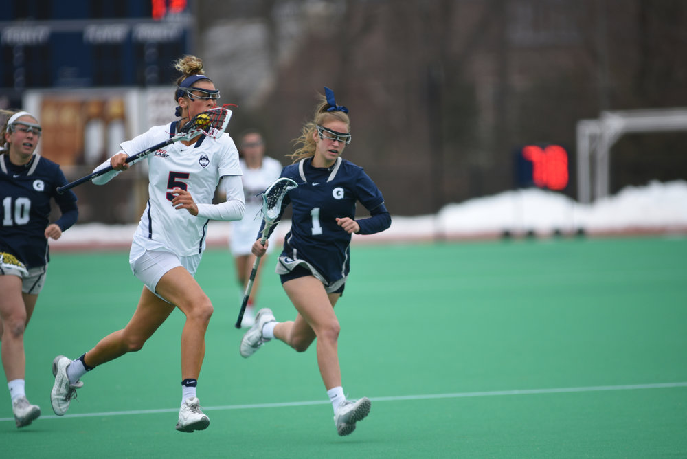 Senior Molly O'Reilly (5) sprints down the field during the Huskies 14-6 loss to the Georgetown Hoyas on March 25, 2017. (Charlotte Lao/The Daily Campus)