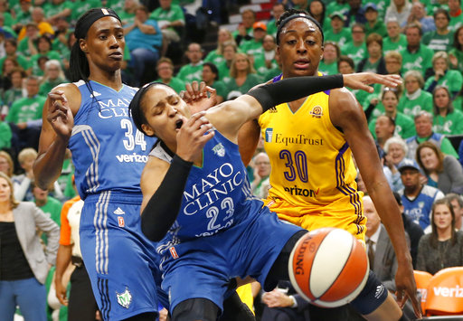 In this Oct. 20, 2016, file photo, Minnesota Lynx's Maya Moore, center, loses the ball in a rebound attempt with Los Angeles Sparks' Nneka Ogwumike, right, in the first quarter during Game 5 of the WNBA basketball finals, in Minneapolis. (AP Photo/Jim Mone, File)