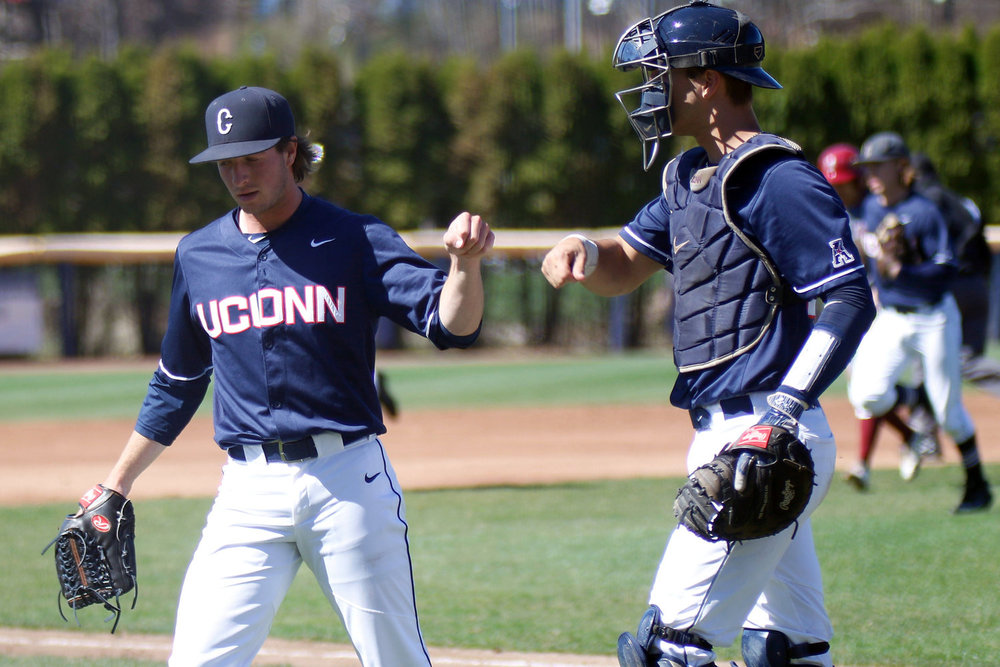 UConn baseball pitcher P.J. Poulin fist bumps catcher Zac Susi after an inning in the Huskies' 11-3 win over UMass-Amherst on Tuesday, April 18, 2017 at J.O. Christian Field.(Ian Bethune/The UConn Blog)