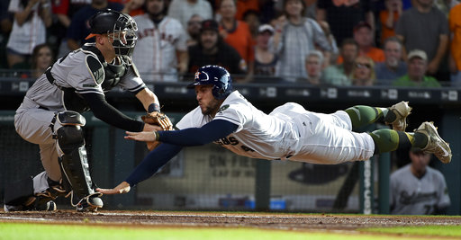 Houston Astros' George Springer, right, dives past Baltimore Orioles catcher Caleb Joseph (36) to score a run on Jose Altuve's RBI double during the first inning of a baseball game, Saturday, May 27, 2017, in Houston. (Eric Christian Smith/AP)