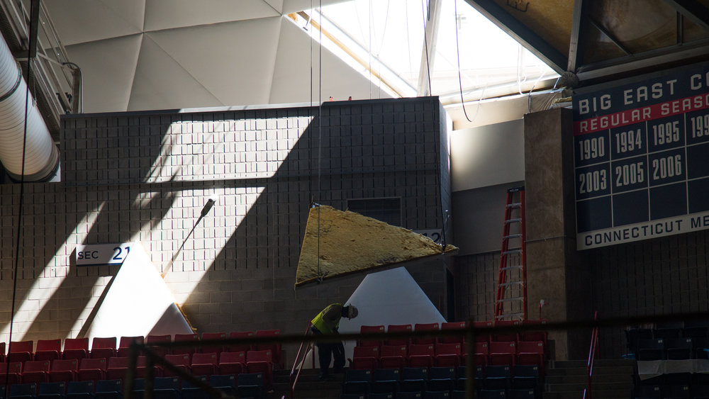 A tile is lowered from the roof as renovations of Gampel Pavilion's roof continues on Wednesday, July 26, 2017. (Amar Batra/The Daily Campus)