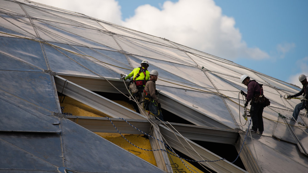 Workers, attached to cables fastening them down, work on renovations of Gampel Pavilion's roof on Wednesday, July 26, 2017. (Amar Batra/The Daily Campus)