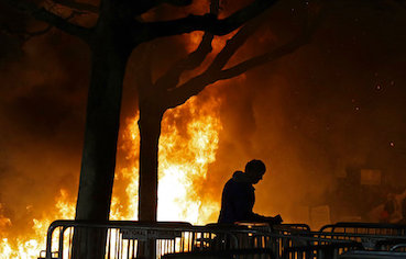In this Feb. 1, 2017 file photo, a fire set by demonstrators protesting a scheduled speaking appearance by Breitbart News editor Milo Yiannopoulos burns on Sproul Plaza on the University of California, Berkeley campus.