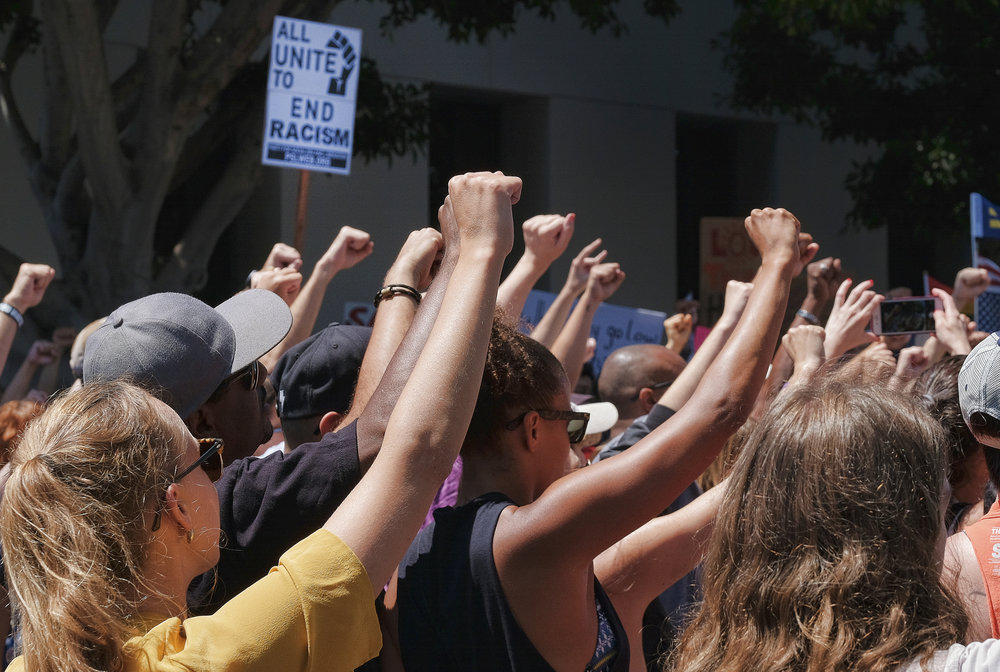 Demonstrators raise clenched fists in defiance to racism during a protest in the Venice beach area of Los Angeles on Saturday, Aug. 19, 2017. Hundreds of people rallied in Southern California to condemn racism in the wake of the deadly events in Charlottesville, Va. (Richard Vogel/AP)