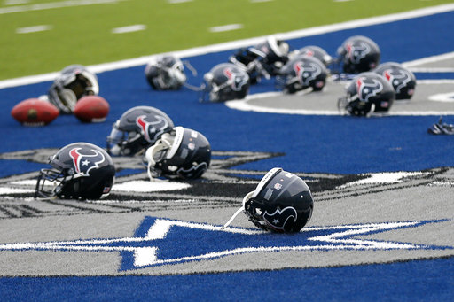 Several Houston Texans helmets sit over the Dallas Cowboys logo in the end zone as the Texans prepare for a morning work out at the Cowboys training facility, Monday, Aug. 28, 2017, in Frisco, Texas. The Texans are working out in the practice facility of the Cowboys because of floods pounding Houston. An exhibition game in the Texans' stadium Thursday might be moved to the home of the Cowboys.(AP Photo/Tony Gutierrez)