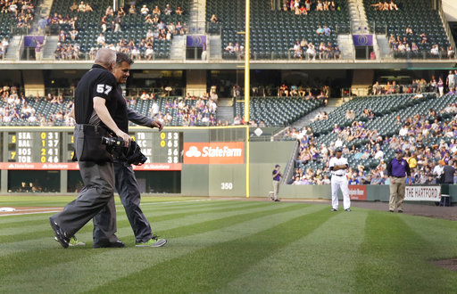Home plate umpire Mike Everitt leaves the game in the middle of the first inning of a baseball game between the Colorado Rockies and the Detroit Tigers on Tuesday, Aug. 29, 2017, in Denver. Everitt left the game after being hit by a warmup pitch from Tigers starter Michael Fulmer. (AP Photo/Jack Dempsey)