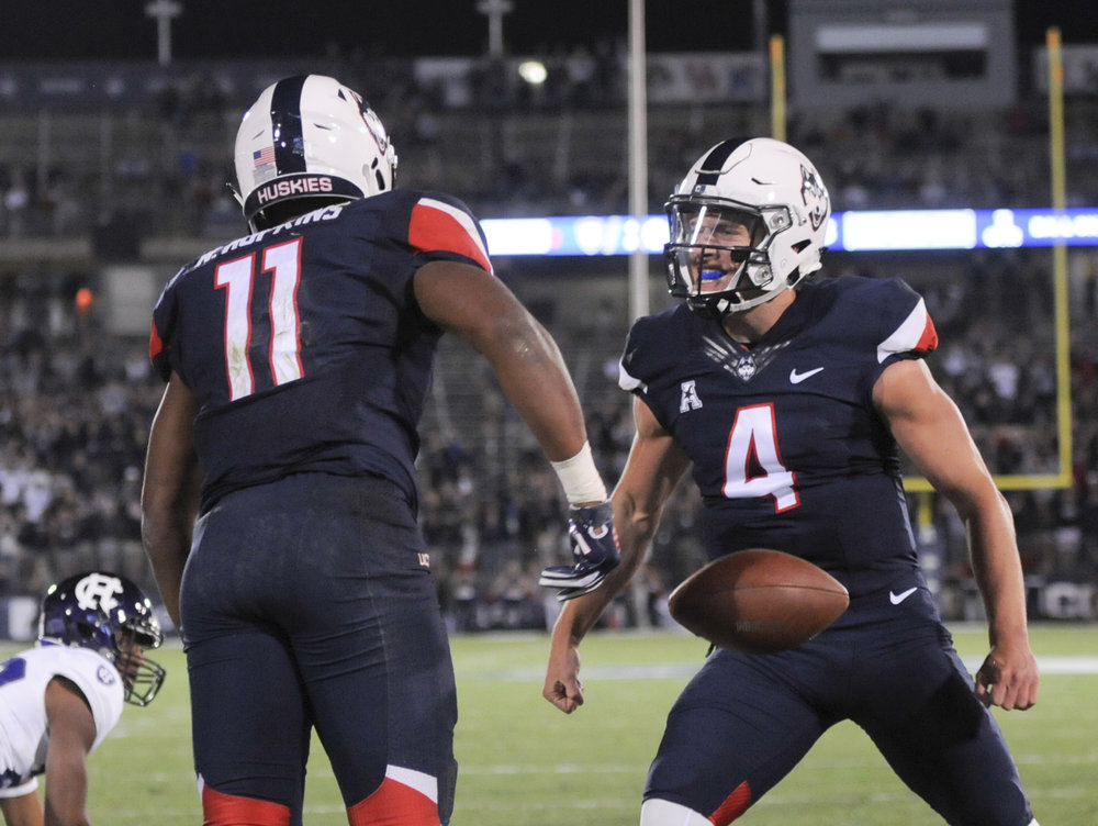 Connecticut running back Nate Hopkins (11) is greeted by quarterback Bryant Shirreffs (4) in the end zone after scoring in the fourth quarter of an NCAA college football game against Holy Cross, Thursday, Aug. 31, 2017, in East Hartford, Conn. (Stephen Dunn/AP)