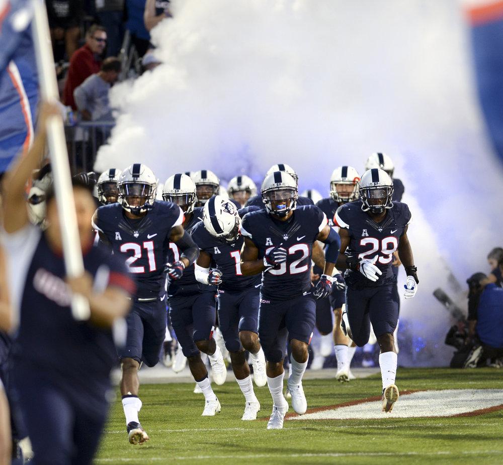 Connecticut takes the field for an NCAA college football game against Holy Cross, its season opener, Thursday, Aug. 31, 2017, in East Hartford, Conn. UConn won 27-20. (Stephen Dunn/AP)