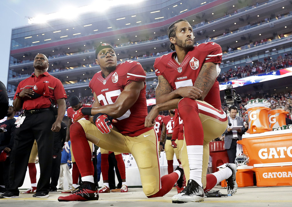 Former San Francisco 49ers' quarterback Colin Kaepernick and Eric Reid kneel during the national anthem on Sept. 12, 2016 before a game against the Los Angeles Rams in Santa Clara, Calif. (Marcio Jose Sanchez/AP)