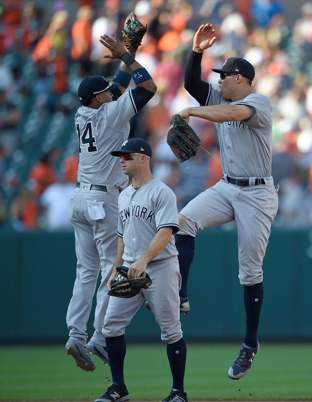 New York Yankees' Starlin Castro (14), Aaron Judge, right, and Brett Gardner, center, celebrate after a baseball game against the Baltimore Orioles, Monday, Sept. 4, 2017, in Baltimore. The Yankees won 7-4. (AP Photo/Nick Wass)