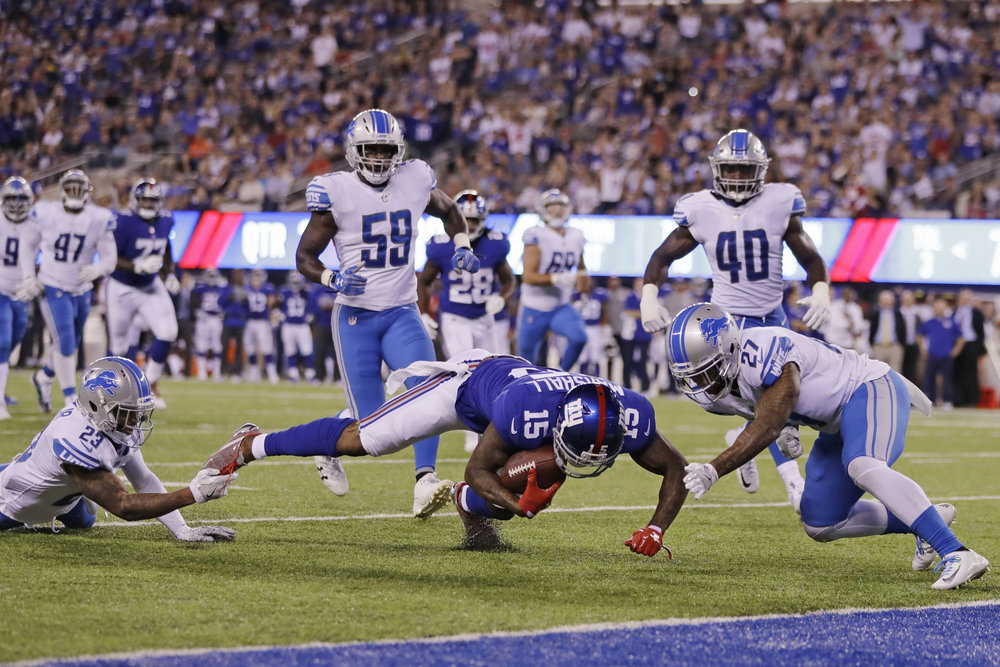 Detroit Lions free safety Glover Quin (27) and Darius Slay (23) tackle New York Giants' Brandon Marshall (15) during the second half of an NFL football game, Monday, Sept. 18, 2017, in East Rutherford, N.J. (Julio Cortez/AP)