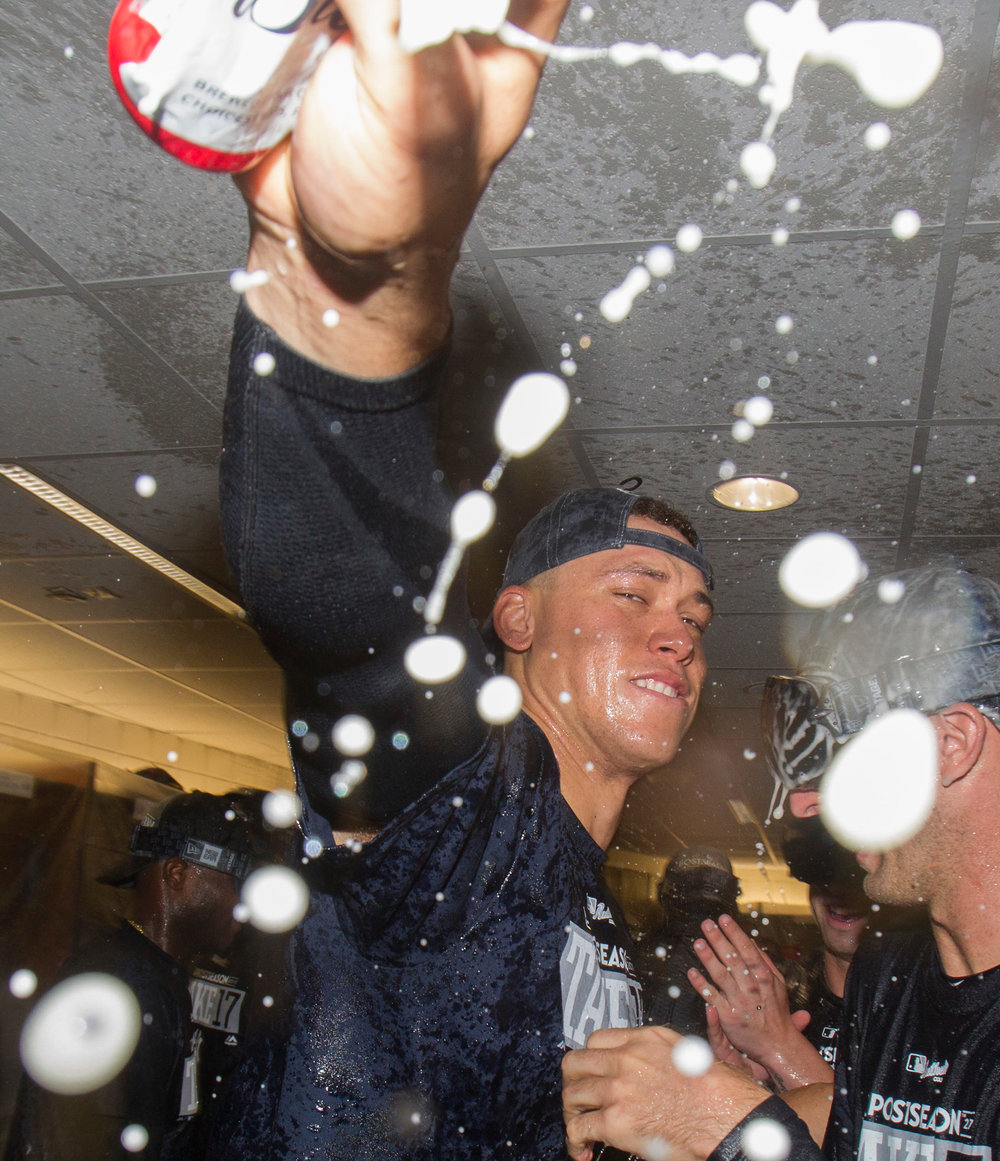 New York Yankees' Aaron Judge celebrates in the locker room after the team clinched a playoff berth by defeating the Toronto Blue Jays in a baseball game in Toronto, Saturday, Sept. 23, 2017. (Fred Thornhill/The Canadian Press via AP)