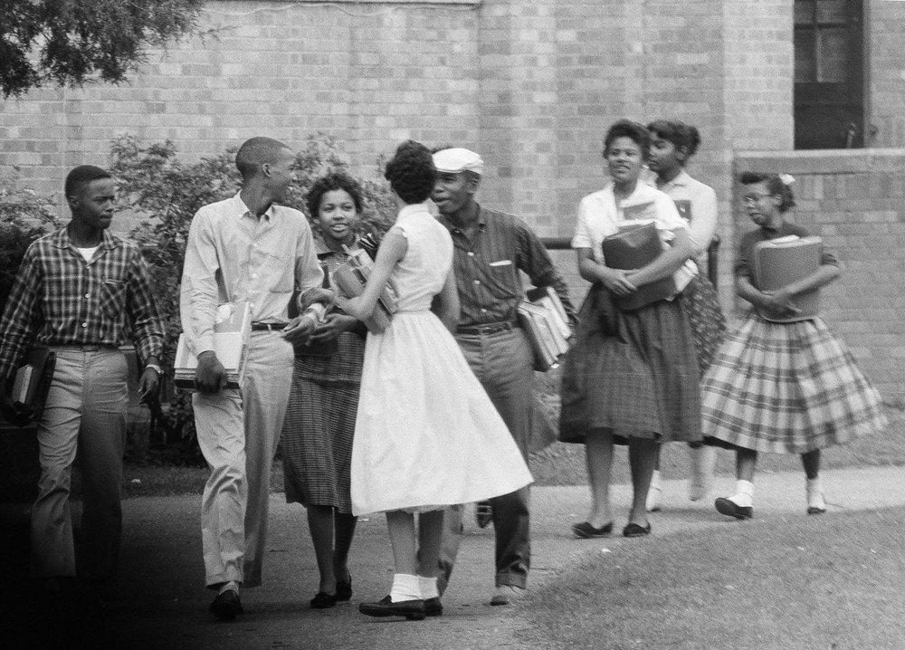 In this Oct. 2, 1957, file photo, the first black students to enroll at Central High School in Little Rock, Ark., leave the building and walk toward a waiting Army station wagon following their classes. Monday, Sept. 25, 2017, marks the 60th anniversary of when nine black students enrolled at the Arkansas school. One of the nine students is obscured by another student in this photograph. (AP Photo/Ferd Kaufman, File)