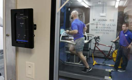 In this Thursday, Sept. 21, 2017 photo, Ryan Curtis, associate director of athlete performance and safety for UConn's Korey Stringer Institute, runs on a treadmill at the institute's Mission Heat Lab in Storrs, Conn., as Luke Belval, the institute's director of research looks on. The new $700,000 lab allows scientists to monitor how athletes, soldiers and others respond to temperatures of up to 110 degrees and 90 percent humidity. (AP Photo/Pat Eaton-Robb)