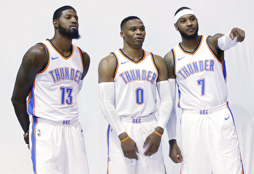 Oklahoma City Thunder's Paul George (13), Russell Westbrook (0) and Carmelo Anthony (7) pose for photos during an NBA basketball media day in Oklahoma City, Monday, Sept. 25, 2017. (AP Photo/Sue Ogrocki)
