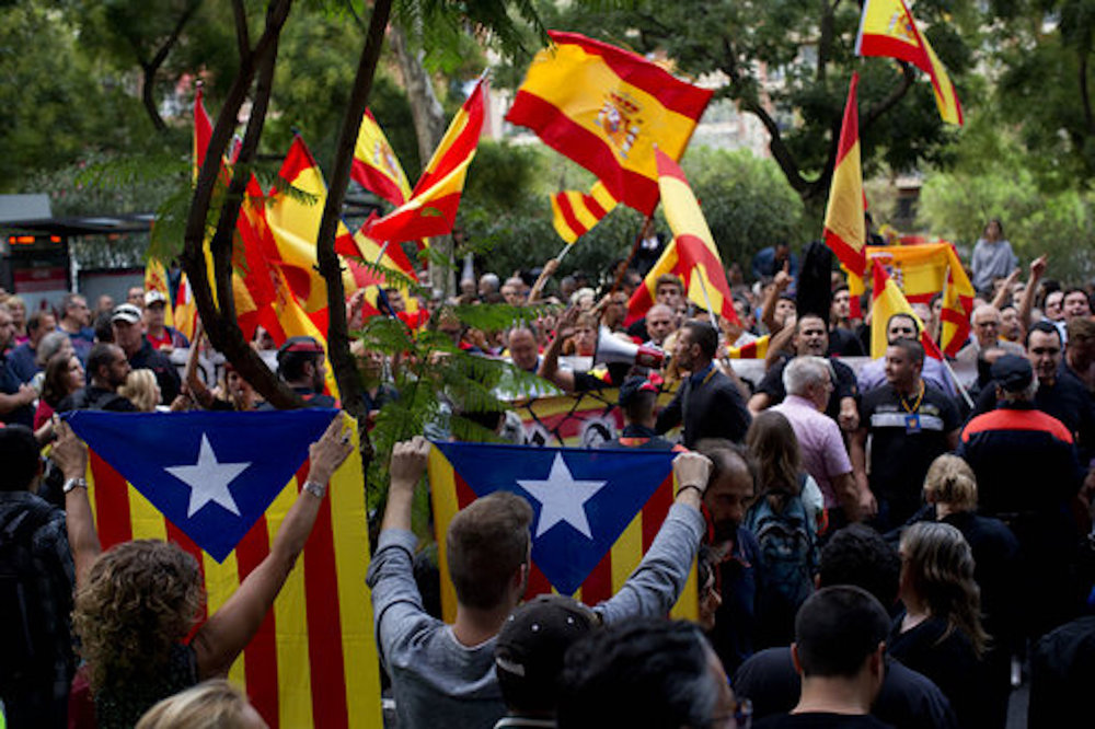 Pro independence demonstrators hold esteladas or independence flags as right wing demonstrators wave Spanish flags, at the background, during a protest in Barcelona, Spain. Dozens of anti independence people demonstrate waving Spanish flags. (AP Photo/Emilio Morenatti)