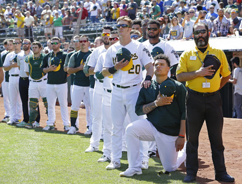 Oakland Athletics' Mark Canha (20) places his hand on the shoulder of Bruce Maxwell as Maxwell takes a knee during the national anthem prior to a baseball game against the Texas Rangers in Oakland, Calif. (AP Photo/Ben Margot, File)