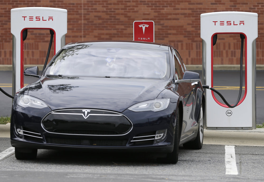 In this Saturday, June 24, 2017, file photo, a Tesla car recharges at a charging station at Cochran Commons shopping center in Charlotte, N.C. (Chuck Burton, File/AP)