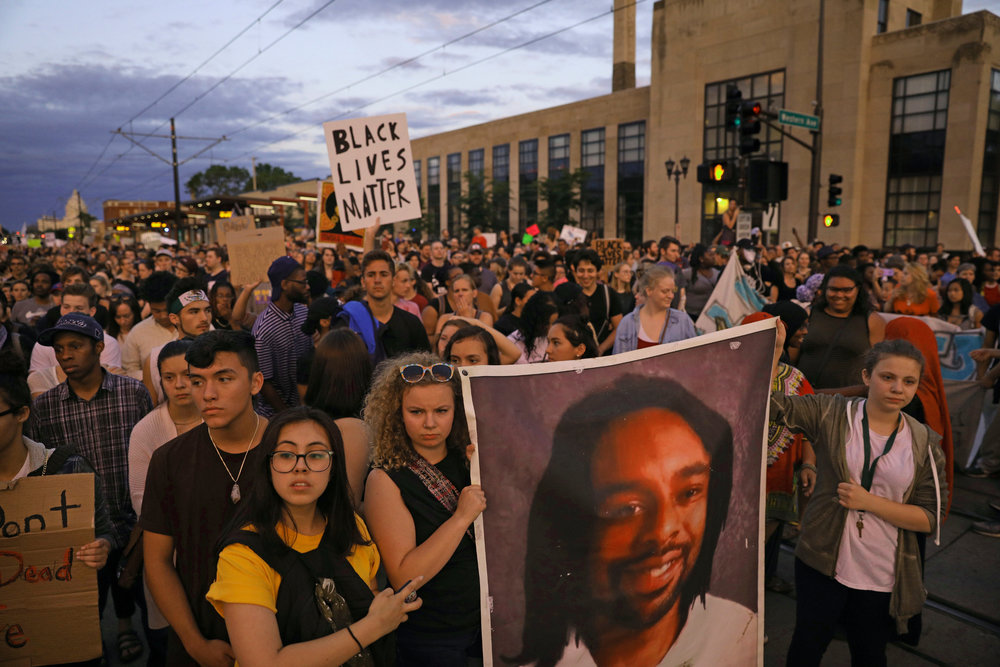 In this June 16, 2017 file photo, supporters of Philando Castile hold a portrait of Castile as they march along University Avenue in St. Paul, Minn. The vigil was held after St. Anthony police Officer Jeronimo Yanez was cleared of all charges in the fatal shooting last year of Castile. Changes to a Department of Justice program that had reviewed police departments in hopes of building community trust have dismayed some civil rights advocates and left some cities wondering what to do next. (Anthony Souffle/Star Tribune via AP File)/Star Tribune via AP File)