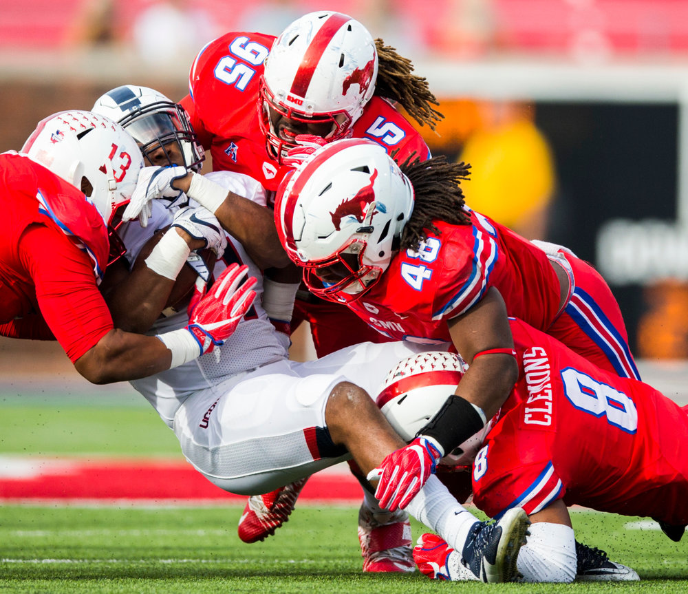 SMU defensive lineman Tyeson Neals (13) defensive tackle J.T. Williams (95) linebacker Anthony Rhone (48) and defensive back Rodney Clemons (8) tackle Connecticut running back Nate Hopkins (11) during the third quarter of an NCAA college football game Saturday, Sept. 30, 2017, in Dallas. (Ashley Landis/The Dallas Morning News via AP)