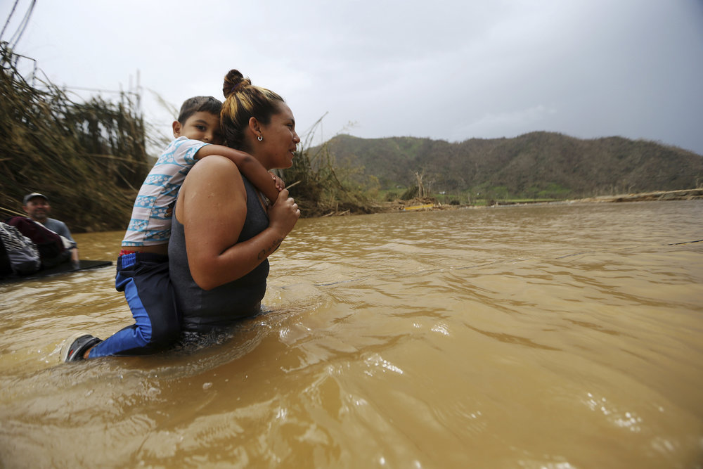 Marlene Ojeda carries her son through the Rio San Lorenzo de Morovis in Puerto Rico, after the bridge that crosses the river was swept away by Hurricane Maria, Wednesday, Sept. 27, 2017. Faculty and students at UConn are working together to help those affected. (Gerald Herbert/AP)