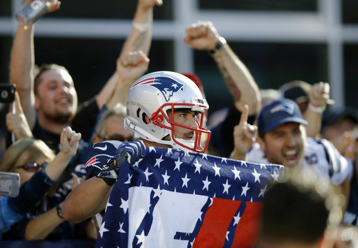 New England Patriots wide receiver Danny Amendola, center, uses a fan's banner to celebrate his touchdown catch against the Carolina Panthers during the second half of an NFL football game, Sunday, Oct. 1, 2017, in Foxborough, Mass. (AP Photo/Charles Krupa)