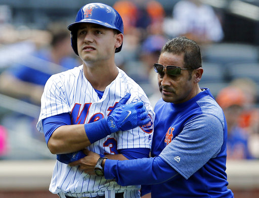 In this Aug. 24, 2017, file photo, New York Mets' Michael Conforto is helped into the clubhouse by team trainer Ray Ramirez after injuring himself swinging his bat during the fifth inning of a baseball game against the Arizona Diamondbacks in New York. The Mets announced Tuesday, Oct. 3, 2017, that trainer Ray Ramirez won't be back in 2018. Ramirez has held that position since 2005. (AP Photo/Adam Hunger, File)